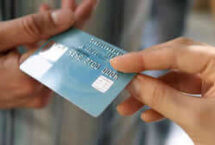 Stock photo of one hand passing a credit card off to another