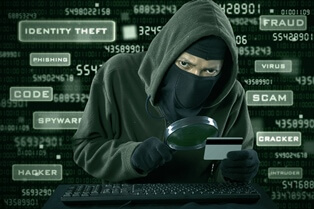 Stock photo of hooded criminal holding a magnifying glass and a credit card