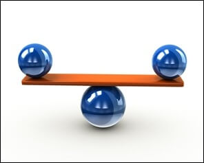 Stock photo of two blue balls balancing on a board above a centered blue ball