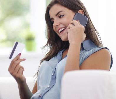 Woman staring at credit card on cell phone