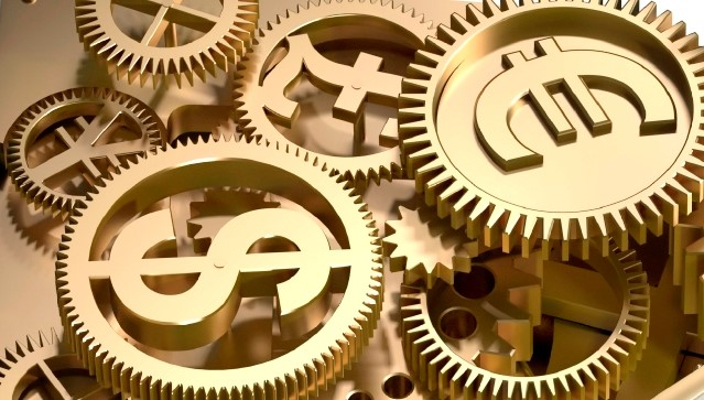Stock photo of golden cogs of international currency symbols