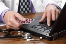 Stock photo of doctor holding pills in one hand while typing on a laptop with the other