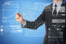 Stock photo of business person drawing numerous graphs and formulas on a clear board