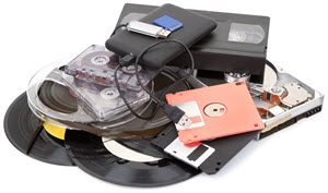 Stock photo of old backup methods: VHS, floppy disks, cassette tapes, vinyl records, a CD drive